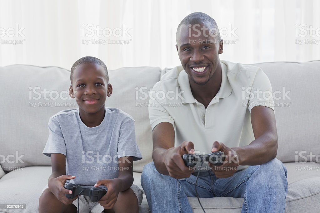 Happy father and son playing video games together royalty-free stock photo