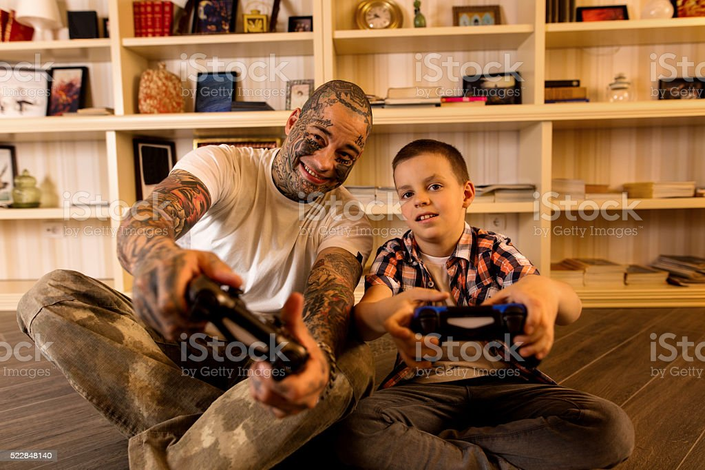 Happy father and son playing video games together. stock photo