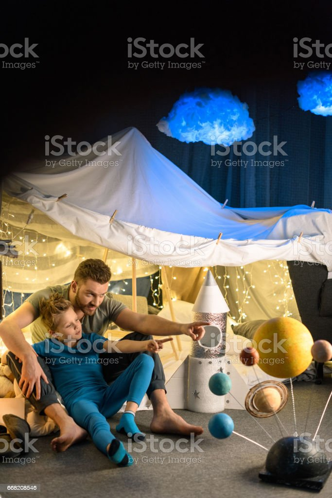 Happy father and son sitting in blanket fort together and looking away stock photo