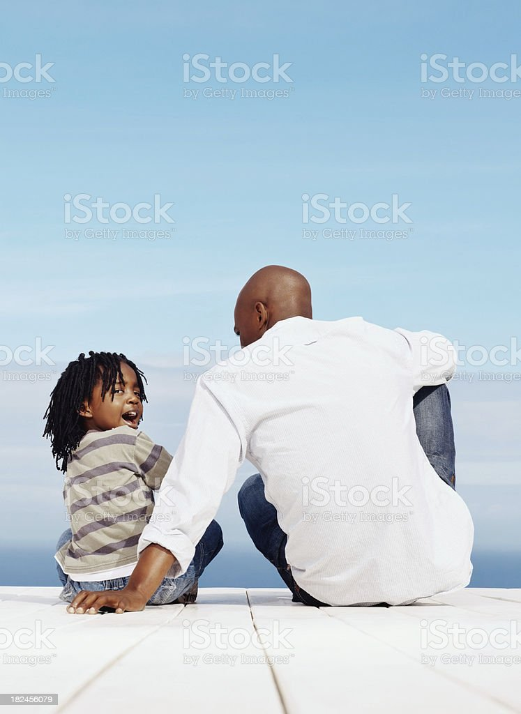 Happy father and son sitting on a wooden porch royalty-free stock photo