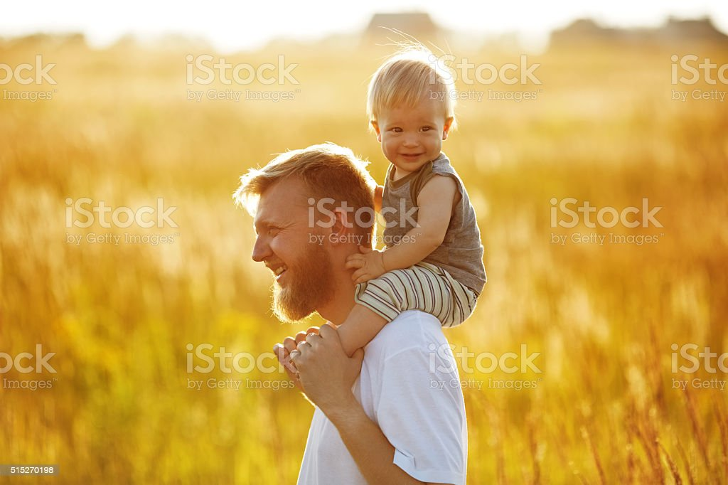 Happy father carries his son stock photo