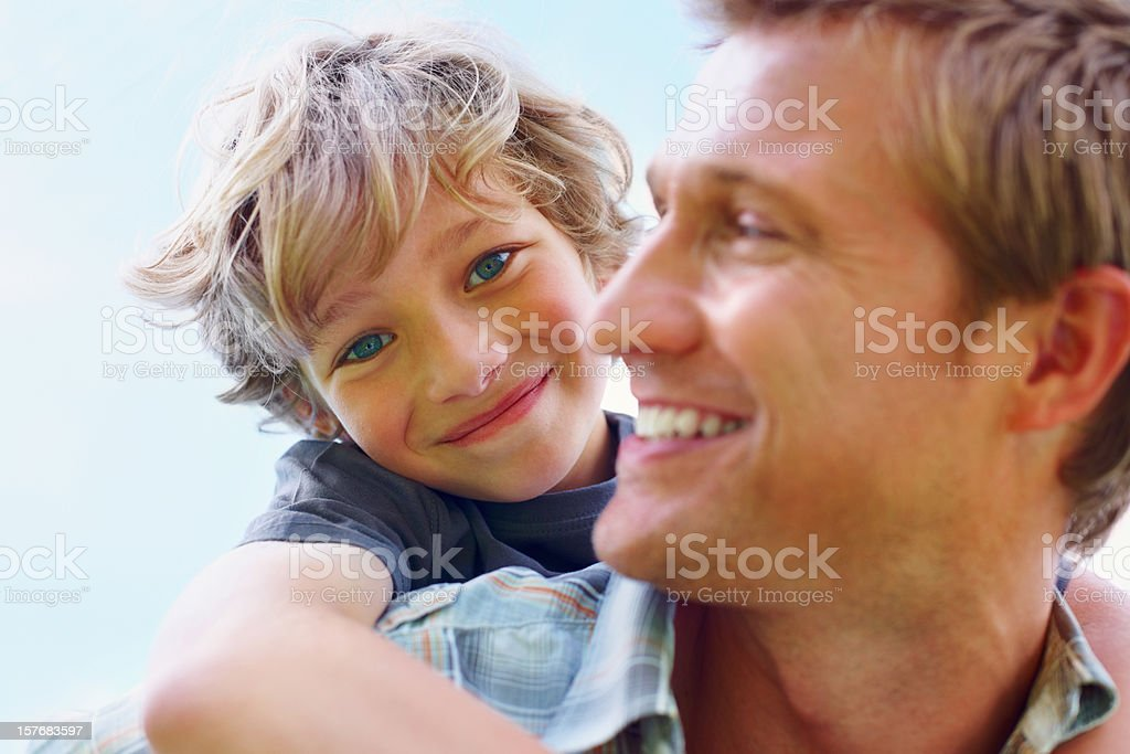 Happy father carrying his son on back against sky royalty-free stock photo