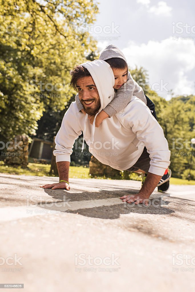Happy father doing push-ups with his little boy in nature. stock photo