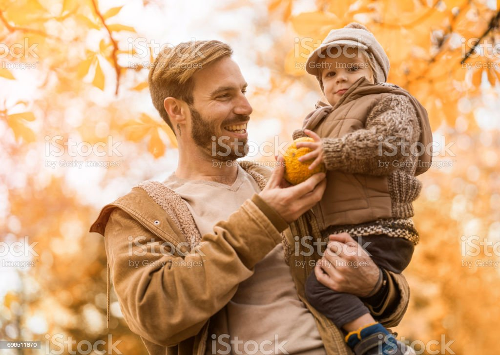 Happy father enjoying with his mall son in autumn day. stock photo