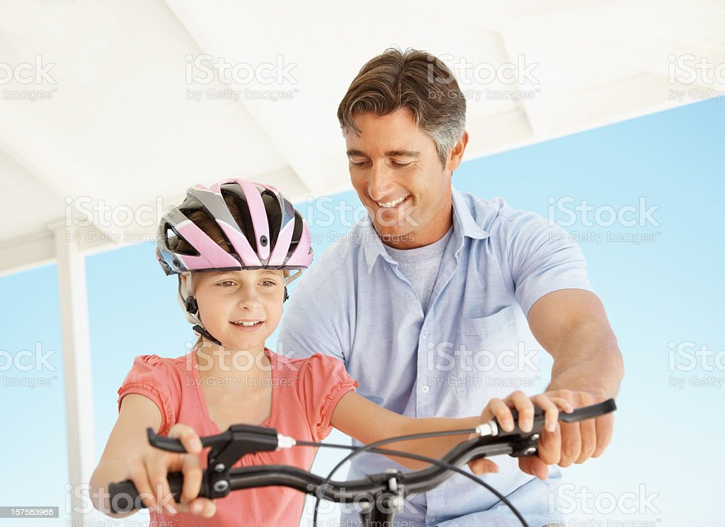 Happy father helping daughter to ride a bicycle royalty-free stock photo