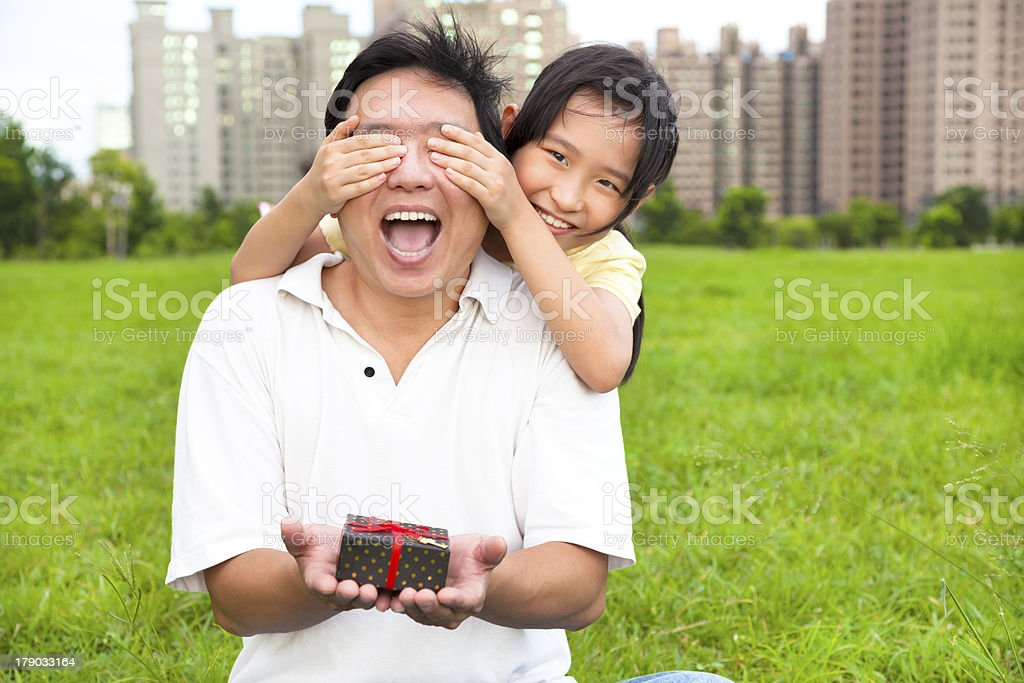 happy father holding gift box from little girl stock photo