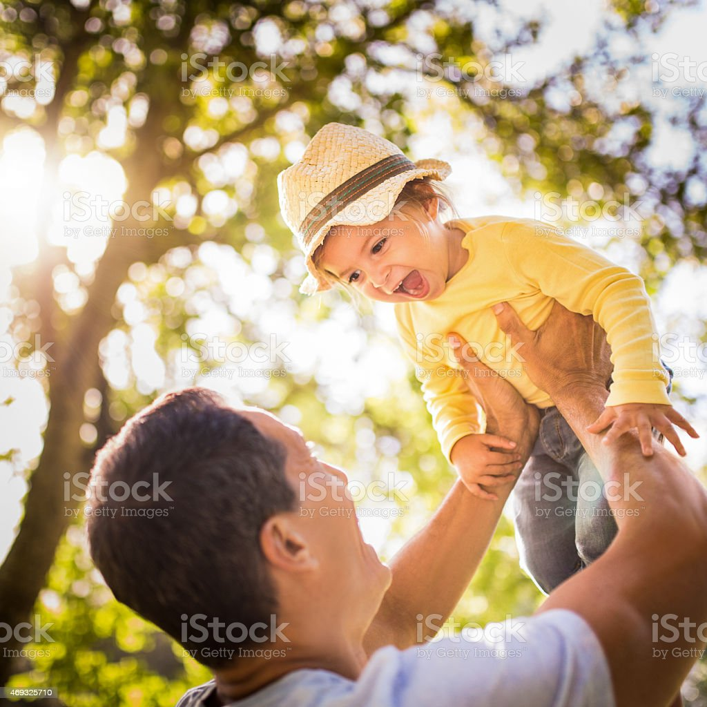 Happy father lifting his laughing little girl playfully stock photo