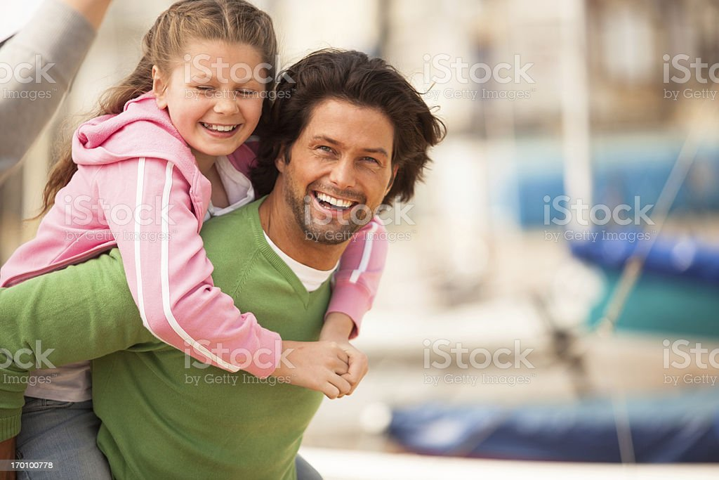 Happy father piggybacking his smiling cute daugther on the beach royalty-free stock photo