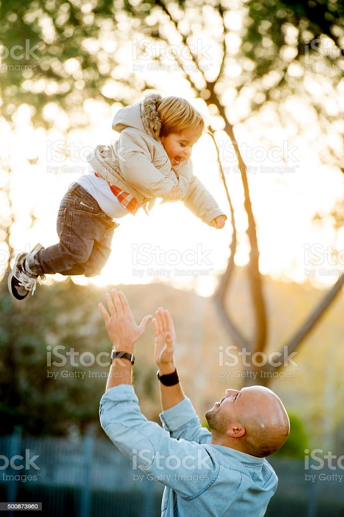 happy father playing with excited little son throwing kid up stock photo
