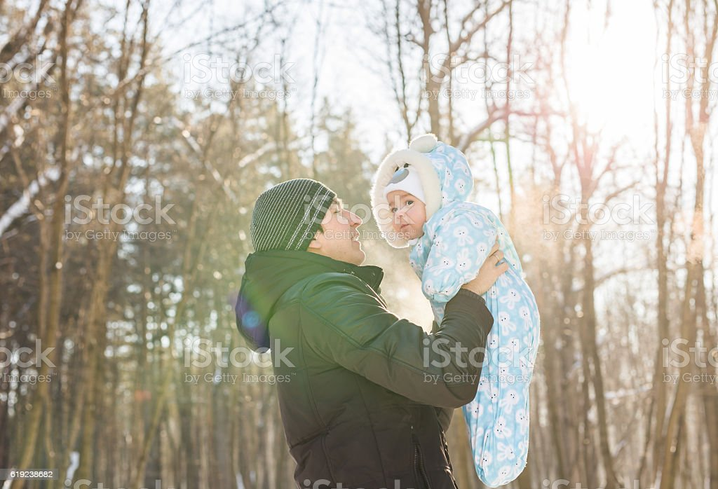 Happy father playing with little child son boy in winter stock photo