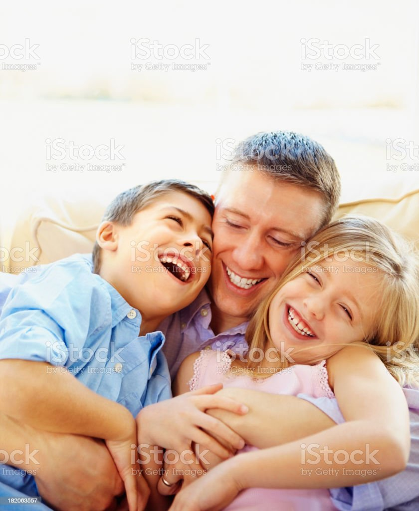 Happy father playing with two children on couch royalty-free stock photo