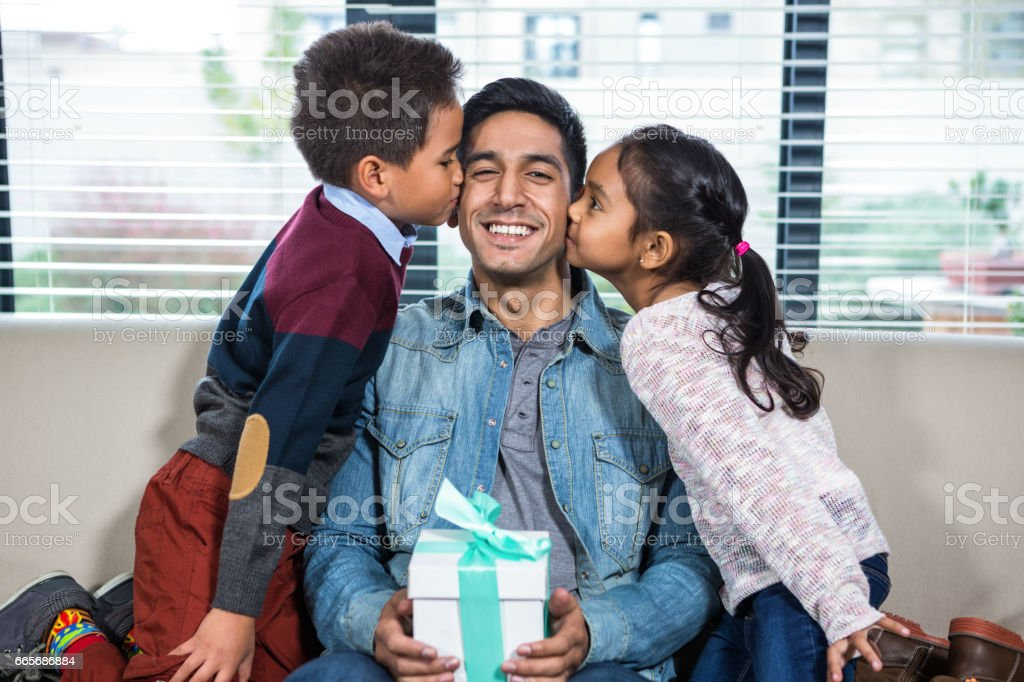 Happy father receiving a gift from his children royalty-free stock photo