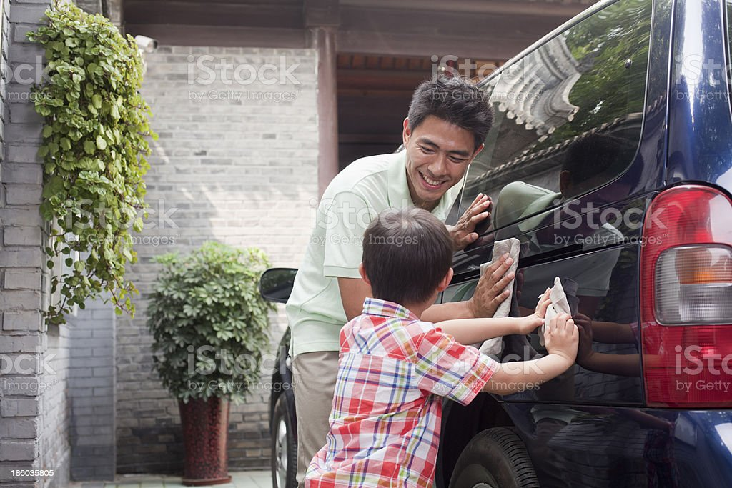 Happy father & son washing a minivan together stock photo