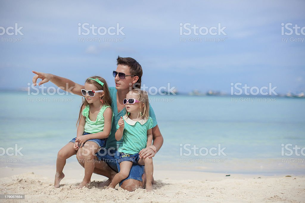 Happy father with two daughters sitting on tropical beach vacation royalty-free stock photo