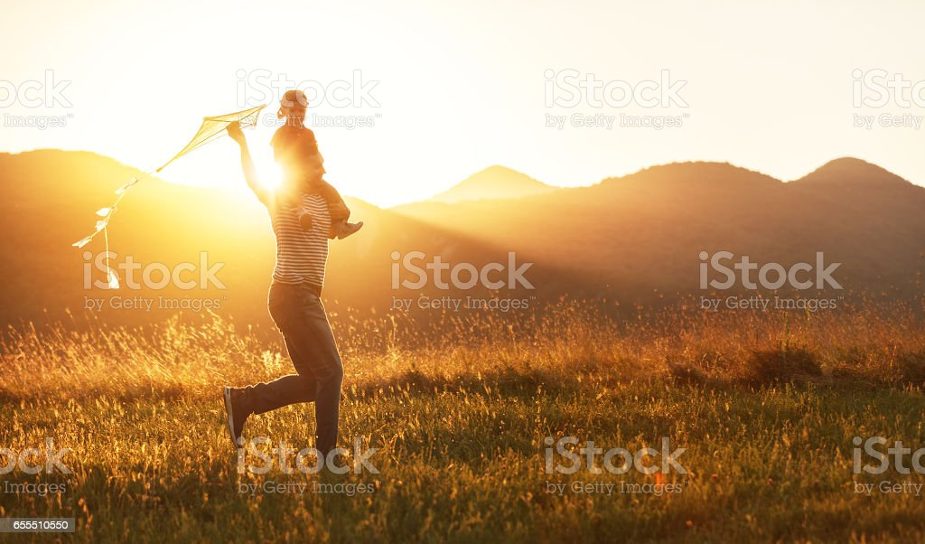 Happy father's day! Child girl and dad with a kite on nature in summer stock photo