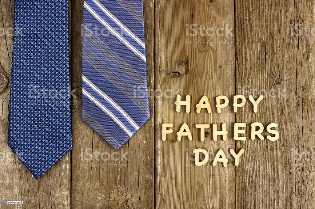 Happy Fathers Day letters with ties on rustic wood stock photo