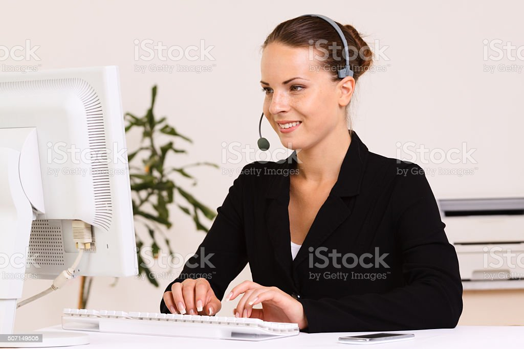Happy female agent in the office on the phone stock photo