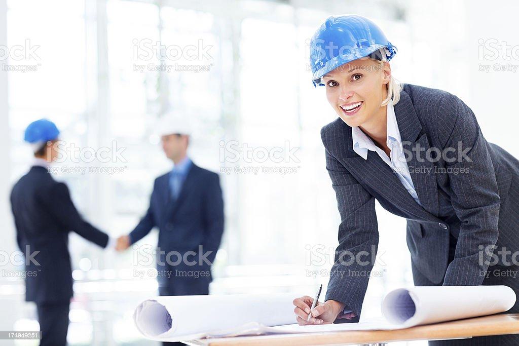 Happy Female Architect Working On Blueprint royalty-free stock photo