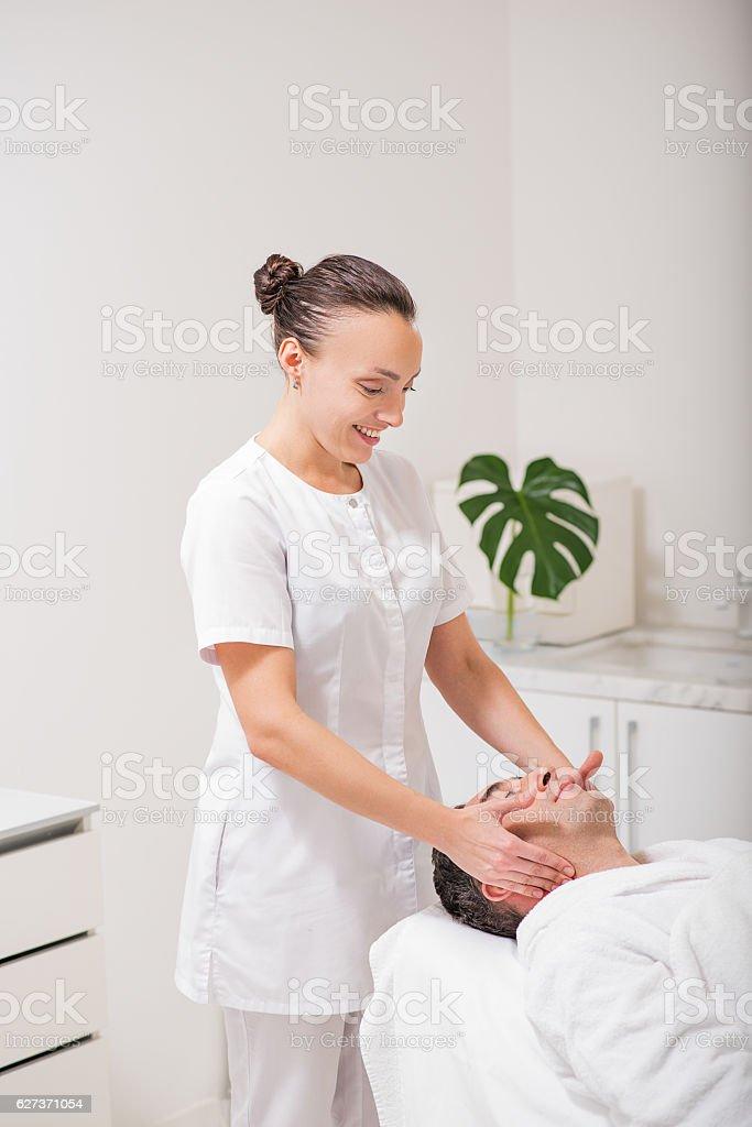Happy female beautician doing facial massage stock photo
