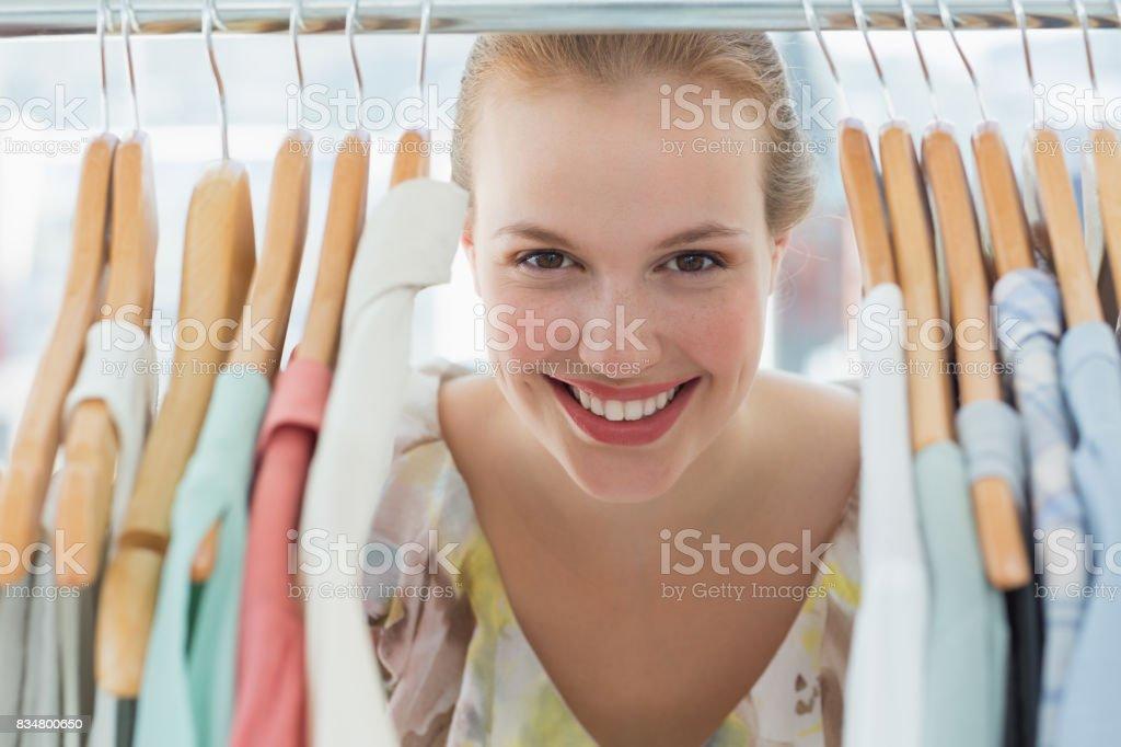 Happy female customer amid clothes rack stock photo