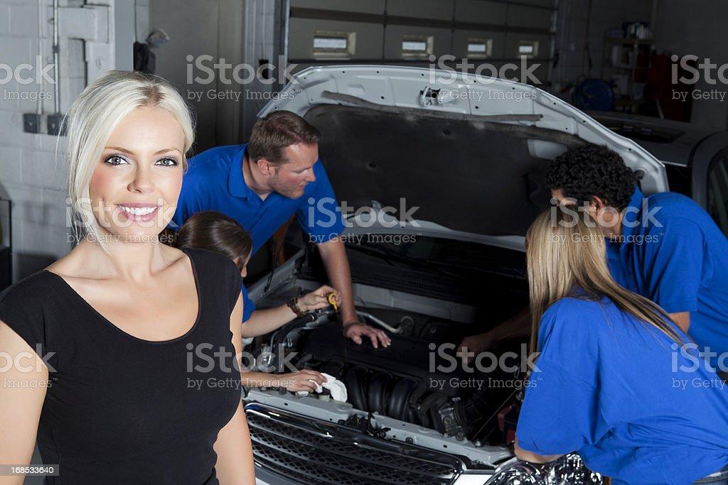 Happy female customer at the body shop mechanic royalty-free stock photo