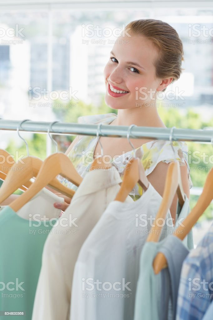 Happy female customer selecting clothes in store stock photo