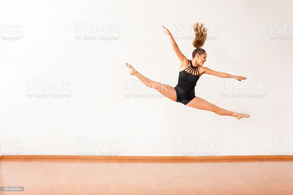 Happy female dancer up in the air stock photo