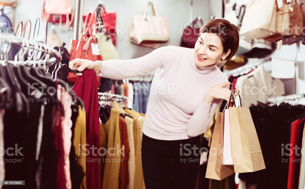 Happy female deciding on pretty blouse stock photo