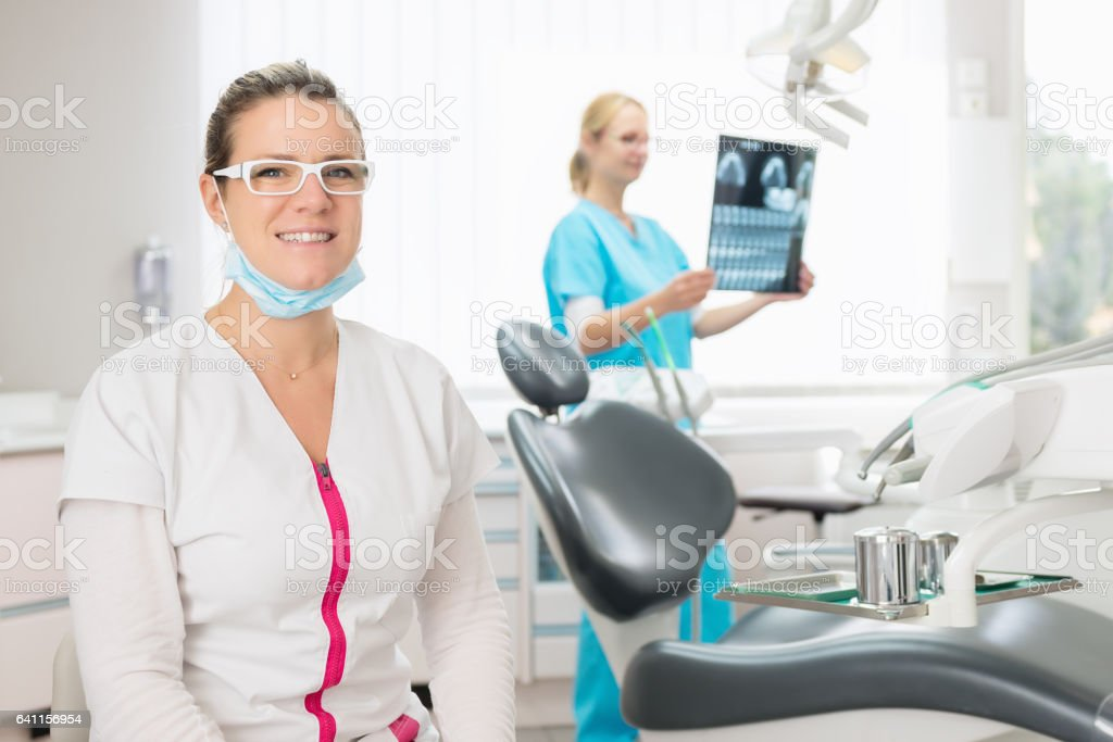 Happy female dentist & dental assistant stock photo