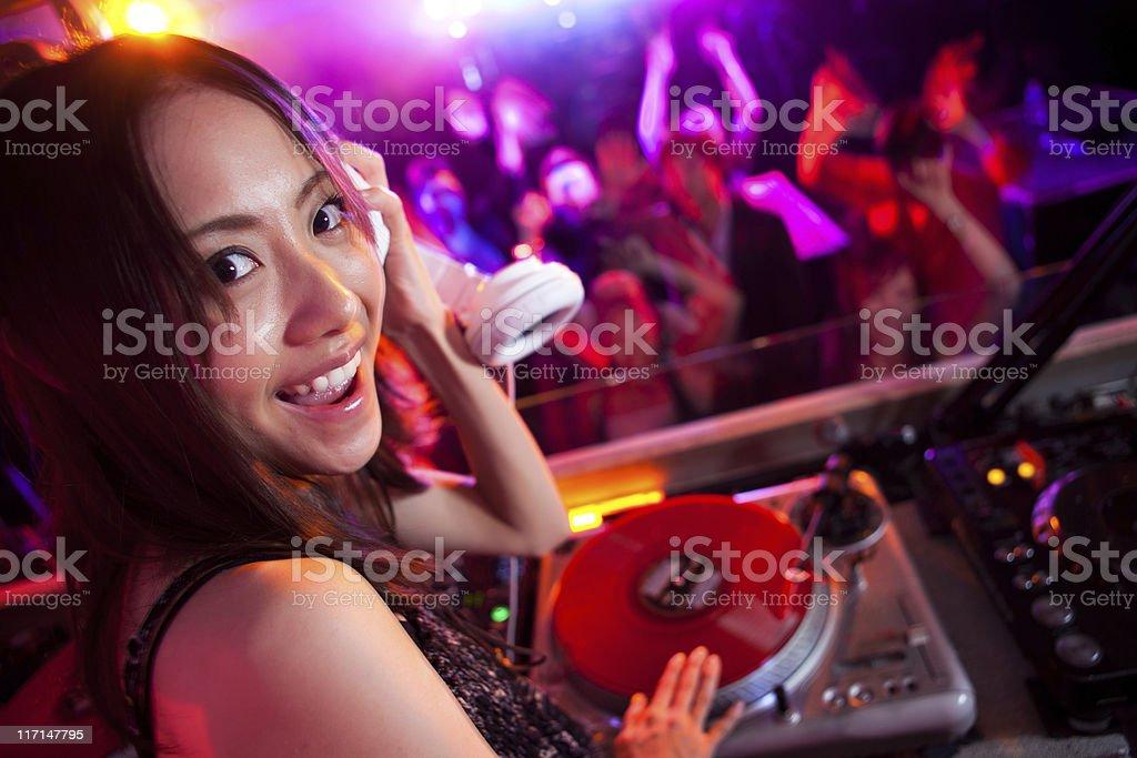 Happy female DJ in a Nightclub stock photo