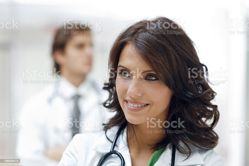 Happy female doctor with colleague in the background royalty-free stock photo