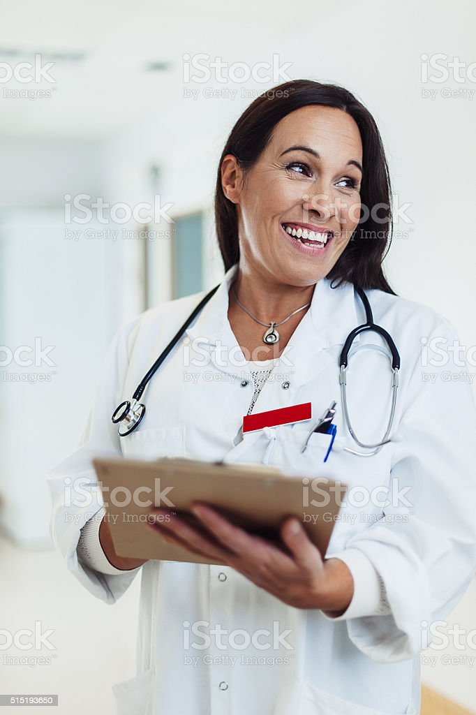Happy female doctor working in hospital stock photo