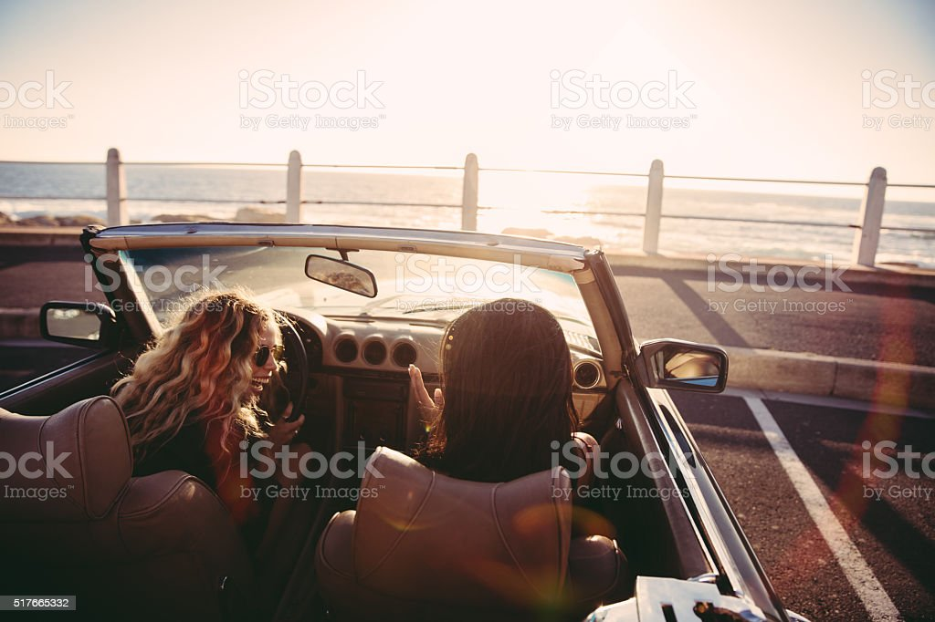 Happy female friends cheering in a convertible at sunset stock photo