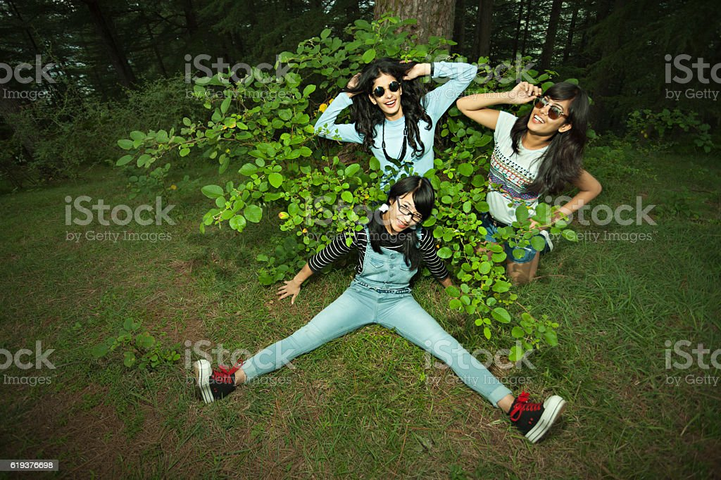 Happy female friends doing fun and posing in nature. stock photo