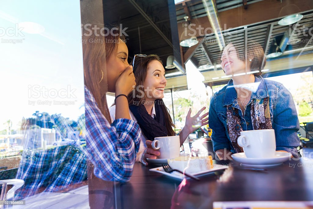 Happy female friends having coffee together in trendy local shop stock photo
