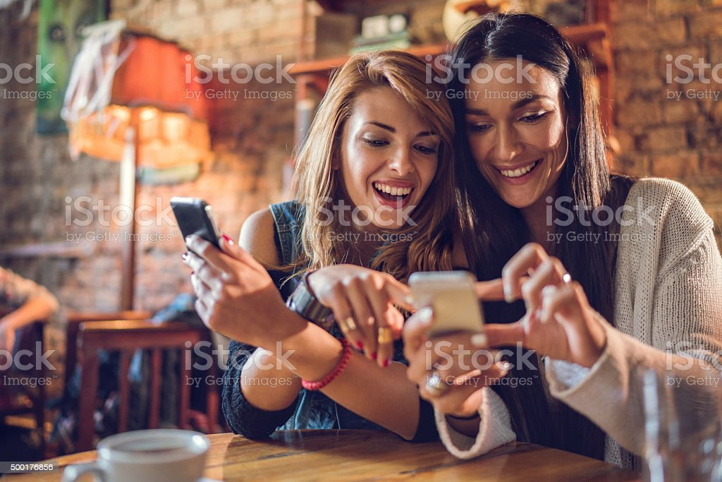 Happy female friends reading a text message on cell phone. stock photo