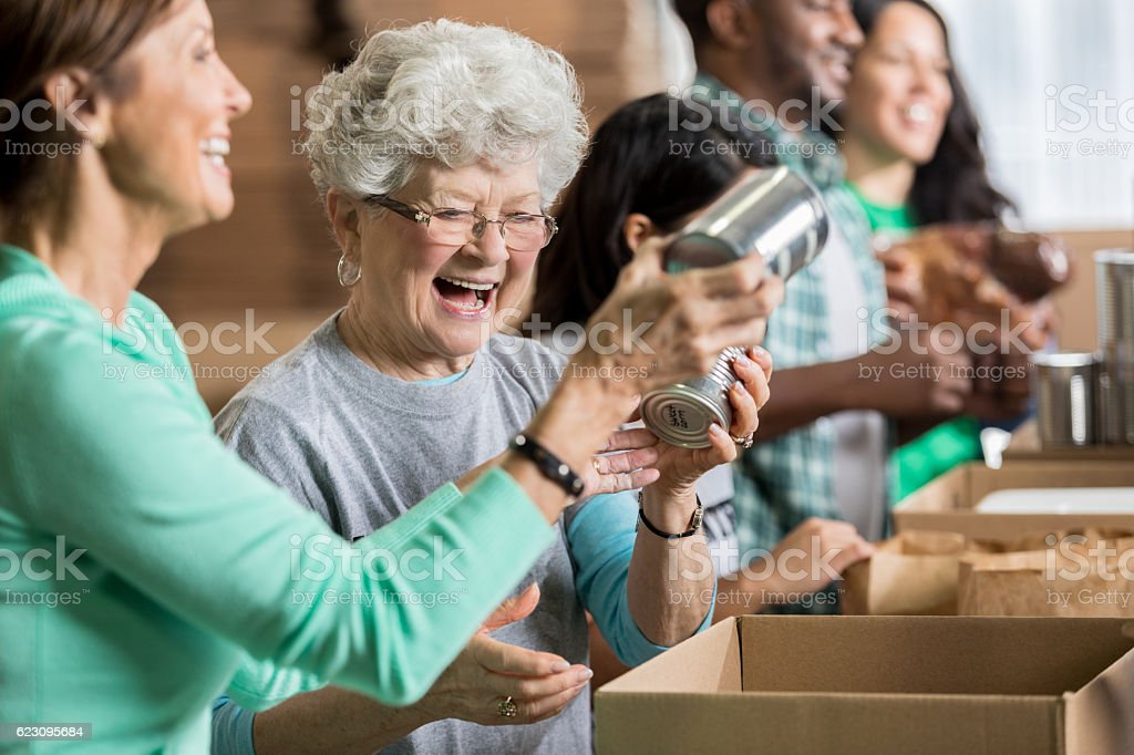 Happy female friends volunteer at charity food bank stock photo