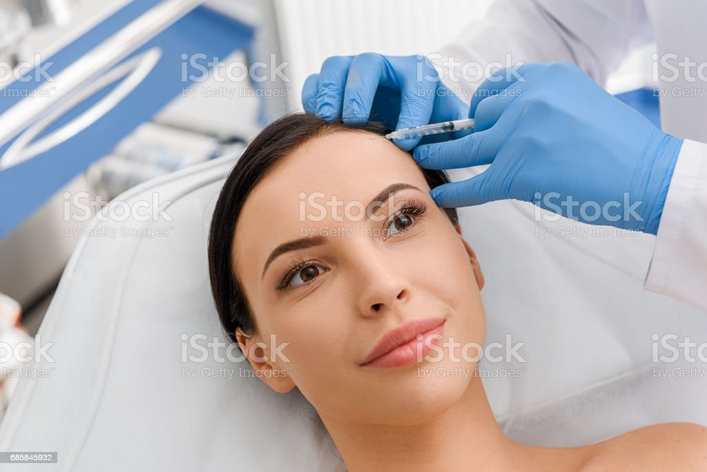 Happy female getting injection in forehead stock photo