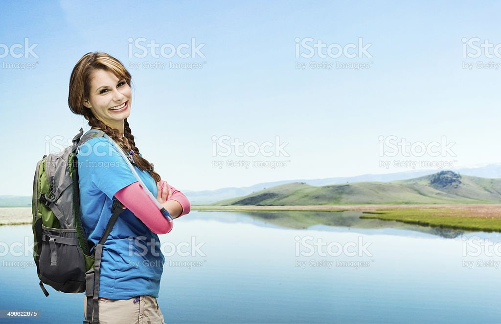 Happy female hiker standing in front of lake stock photo
