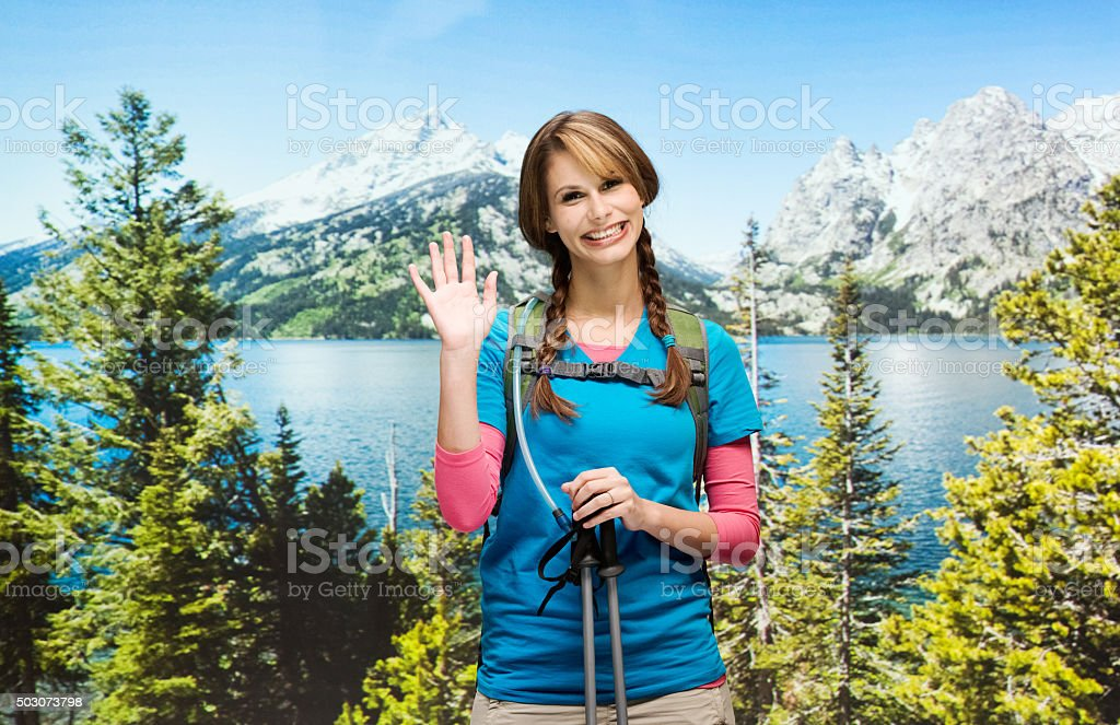 Happy female hiker waving hand in wilderness area stock photo