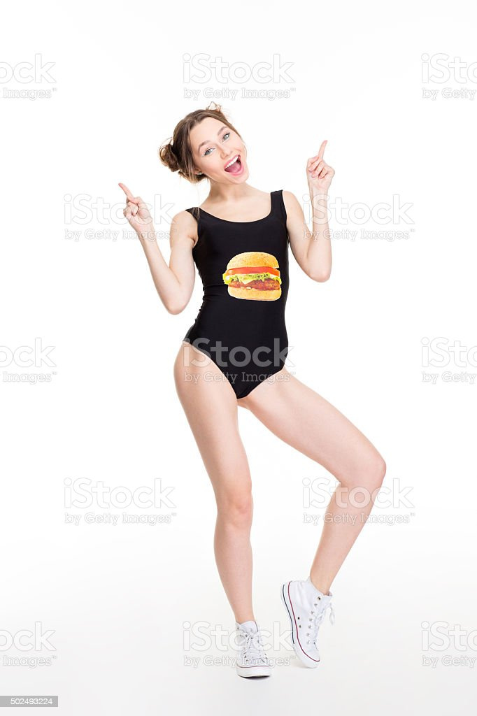 Happy female in designer swimwear pointing up with both hands stock photo