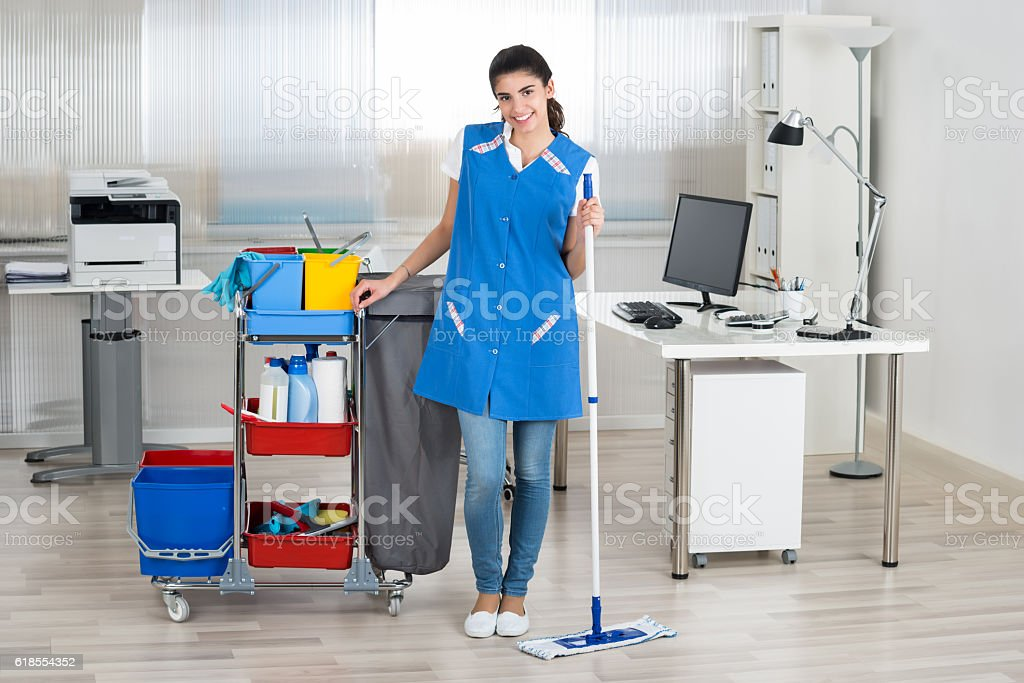 Happy Female Janitor Mopping Floor In Office stock photo