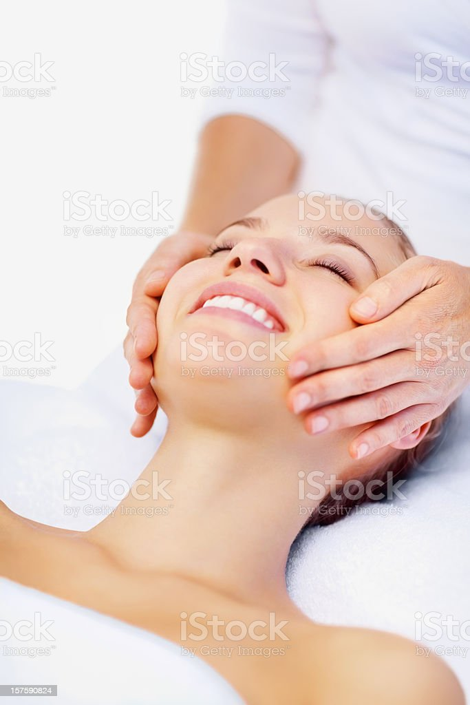 Happy female receiving a facial massage royalty-free stock photo