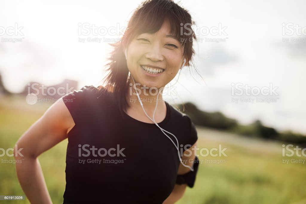 Happy female running standing outdoors and smiling stock photo