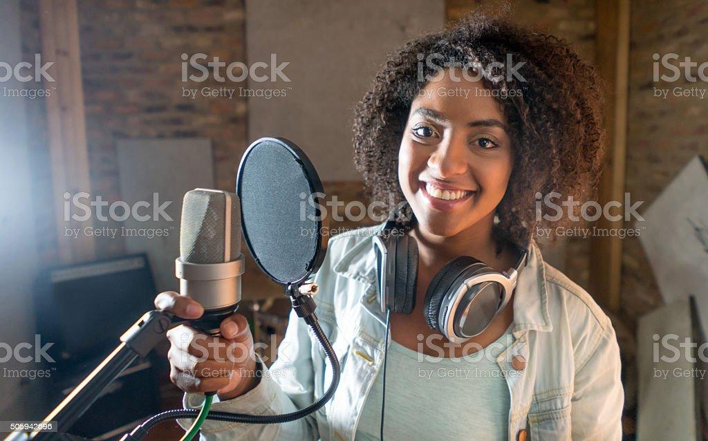 Happy female singer at a recording studio stock photo