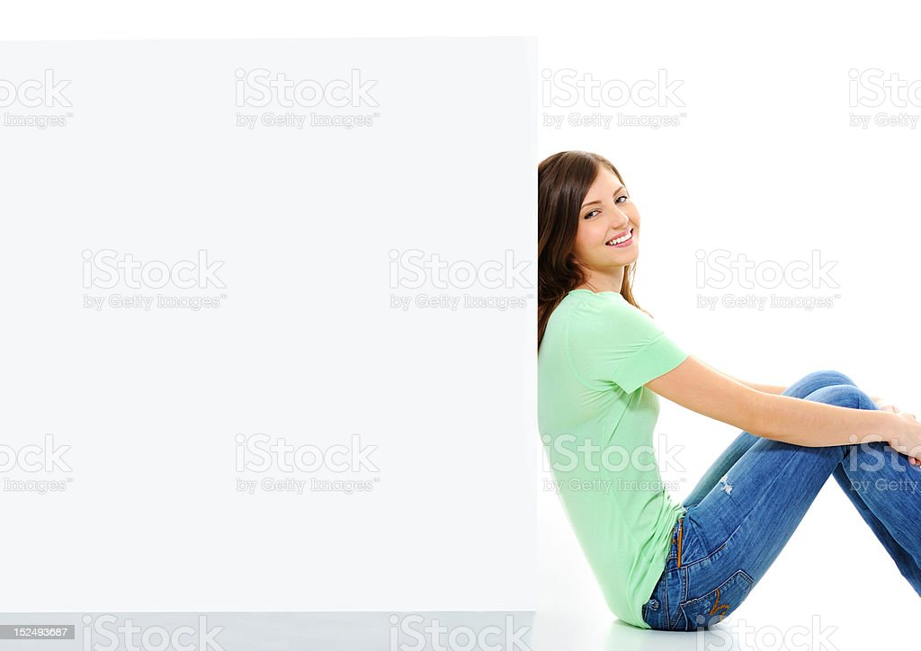 happy female sitting on the floor near white blank banner royalty-free stock photo
