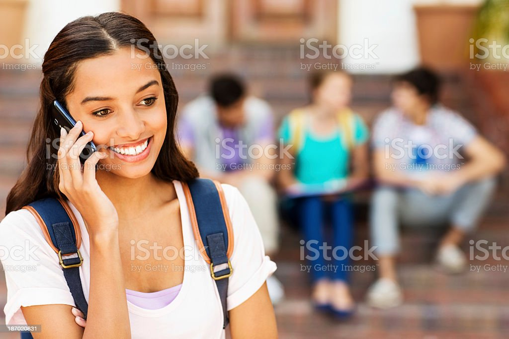 Happy Female Student Answering Smart Phone On Campus royalty-free stock photo