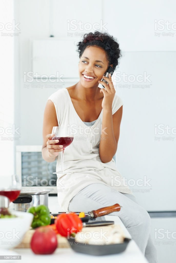 Happy female talking on cellphone while holding wineglass royalty-free stock photo