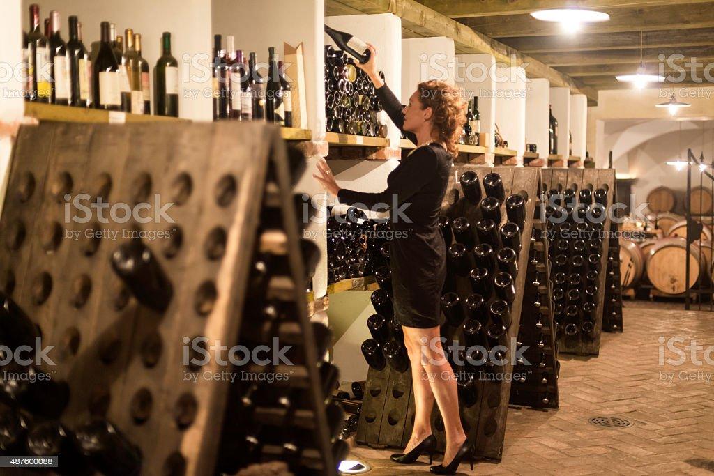 Happy Female Vintner Checking Wine Bottles, Cellar in Europe stock photo