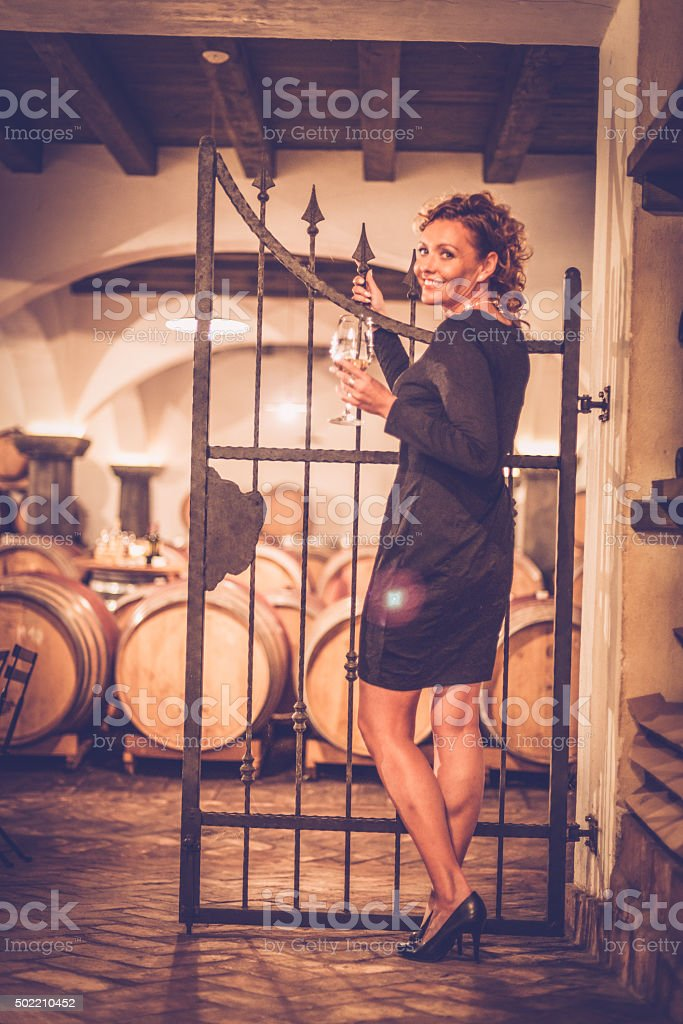 Happy Female Vintner Tasting White Wine, Cellar in Europe stock photo